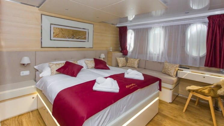 Riva Croatia small ship main deck cabin with large bed, wood accents and window with a curtain behind it