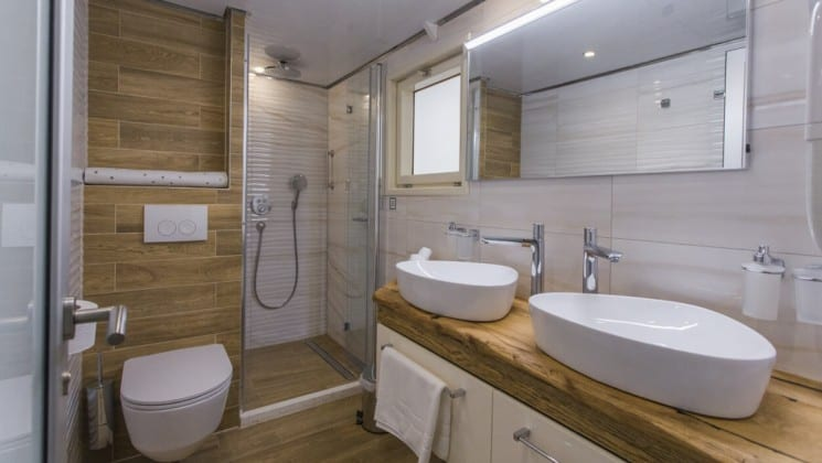 Riva Croatia small ship bathroom with 2 sinks, large shower, toilet and wood accents