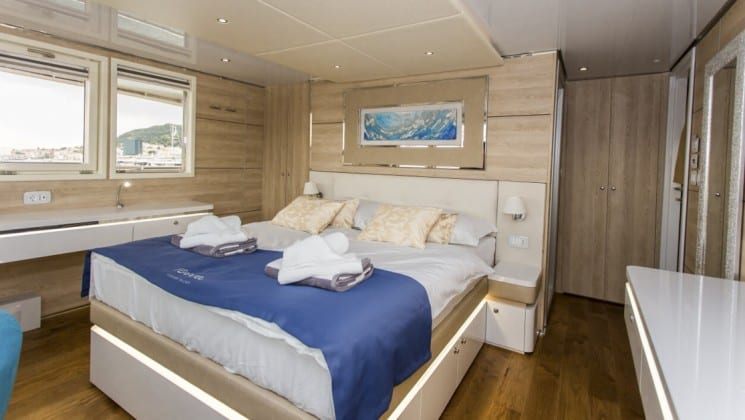 Riva Croatia small ship vip cabin with large bed, wood floors and large window