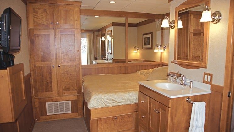 Safari Explorer Hawaii small ship single room with bed, large mirror behind the bed and nightstand, all with wood accents