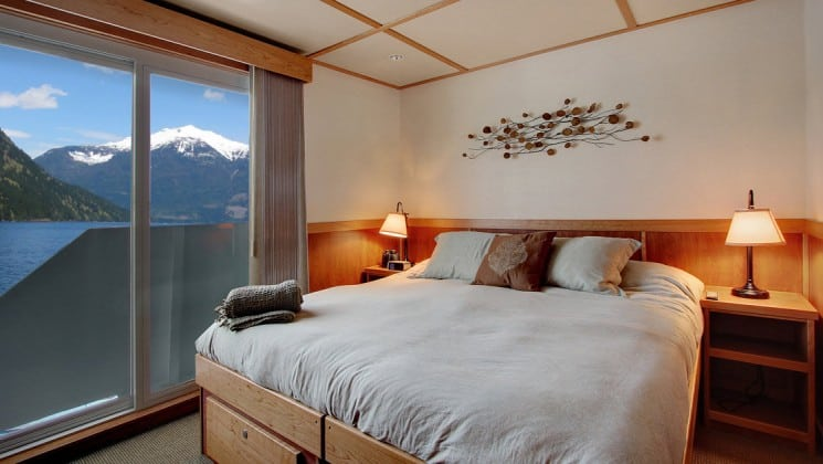captain stateroom with large bed with pillows on it and a large window behind it aboard the Safari Quest pacific northwest small ship