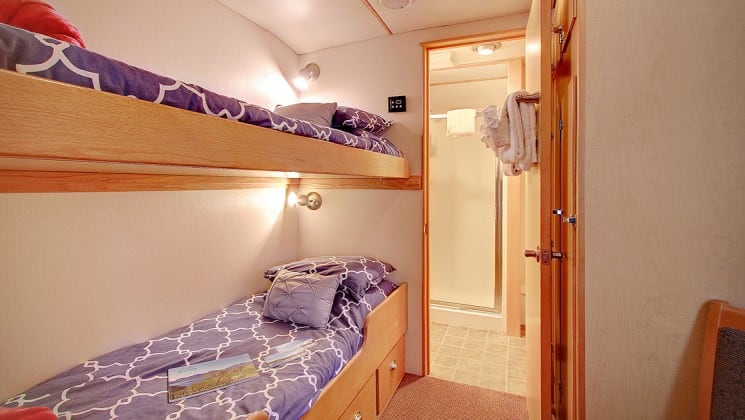 single cabin aboard the Safari Quest Alaska small ship, with bunk beds and a door leading into the bathroom
