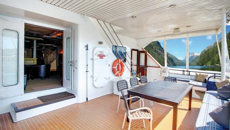 outside deck with a table and chairs, a door leading inside and large windows aboard the Safari Quest Alaska small ship