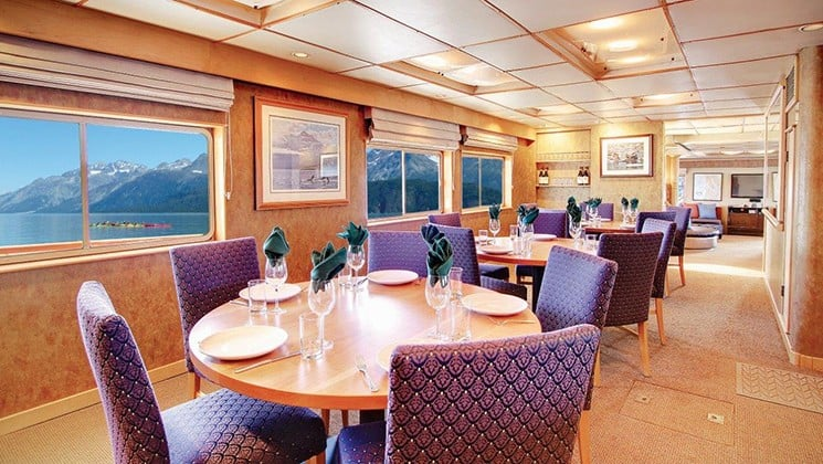 dining room with rows of tables and chairs, and rows of windows aboard the Safari Quest san juan islands small ship