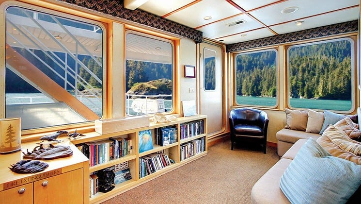 the library aboard Safari Quest Alaska small ship with a bookshelf, comfortable chairs and large windows looking out at the wilderness