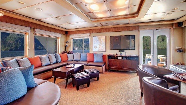the lounge aboard Safari Quest Alaska small ship, with a coffee table and ottomans, windows, couch with pillows and a table and chairs