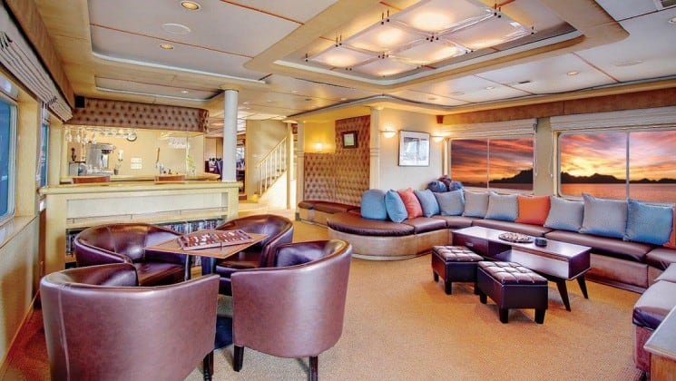 Safari Quest san juan islands small ship lounge with a table and chairs, sofa and bar