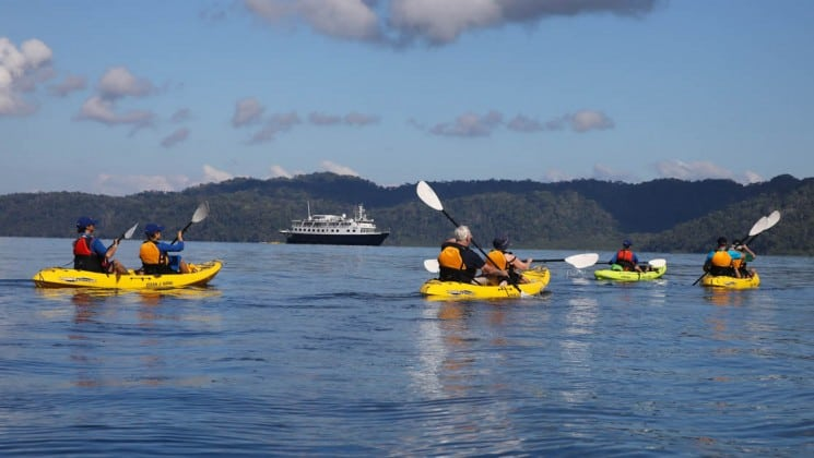 adventure travelers kayaking on calm waters on a sunny day with the Safari Voyager Panama small ship in the background