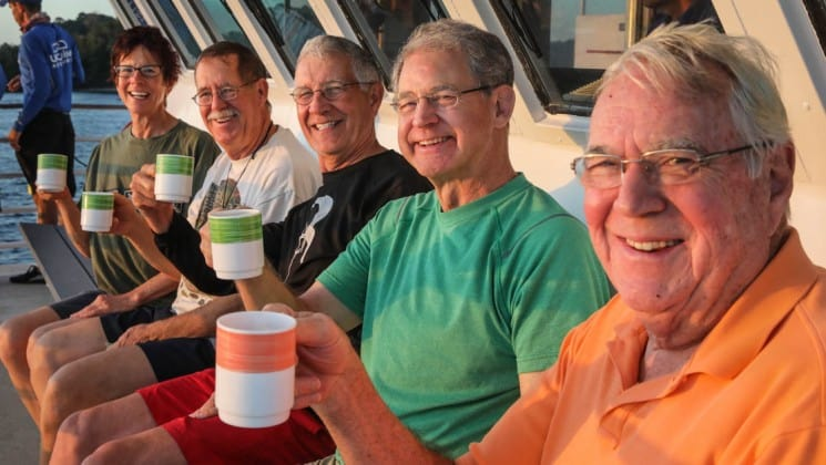 a group of adventure travelers sitting lined up raising their glasses on the deck of the Safari Voyager Costa Rica small ship