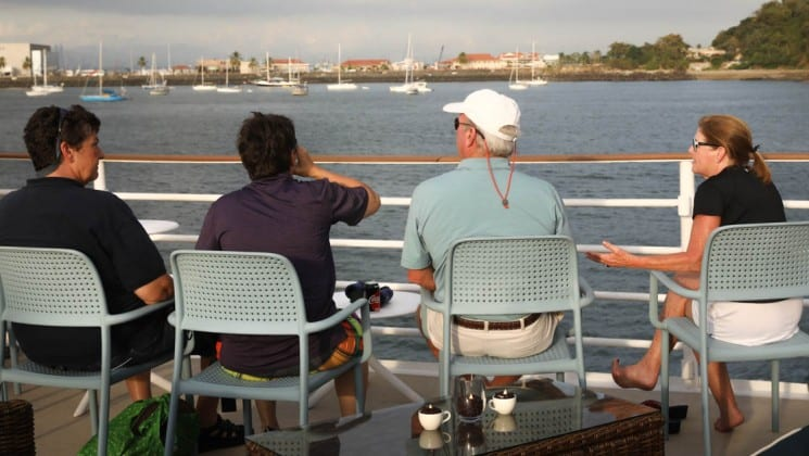 a row of adventure travelers relax on the deck of the Safari Voyager Panama small ship and look out at the ocean