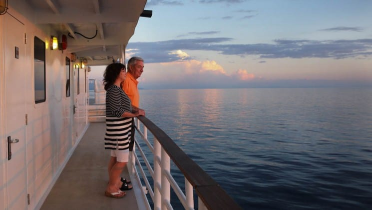 baby boomer couple standing on the balcony of the Safari Voyager Costa Rica small ship while the sun sets