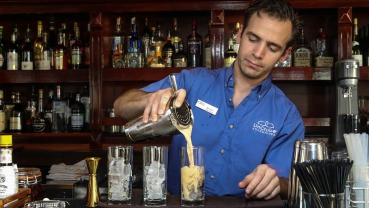 bartender pouring a drink into a glass with a shelf of bottles behind him aboard the Safari Voyager Costa Rica small ship