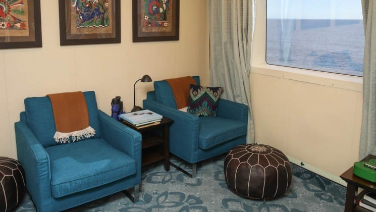 library with 2 blue chairs and a large window aboard the Safari Voyager Costa Rica small ship