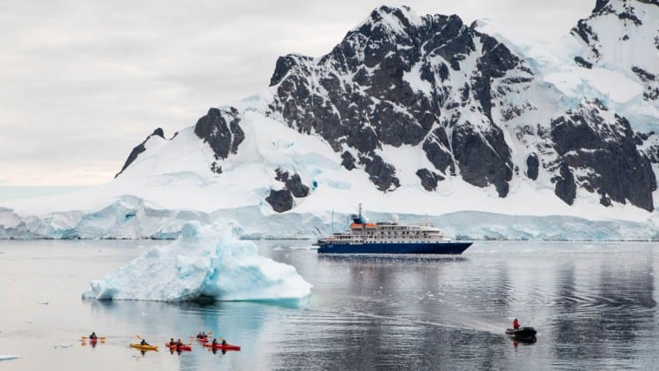 Distant view of Sea Spirit expedition ship's starboard side with kayakers near iceberg