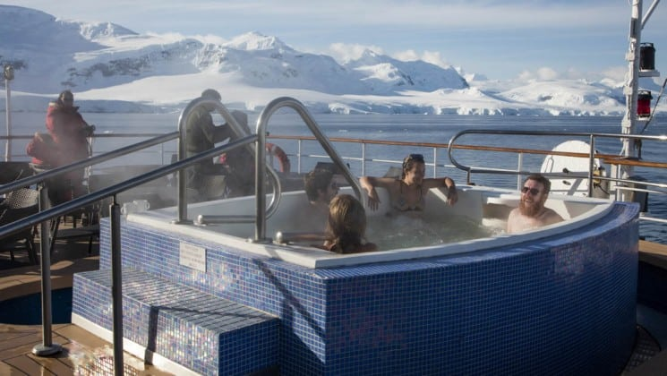 Four guests in Jacuzzi on deck of Sea Spirit expedition ship, with glaciers in background