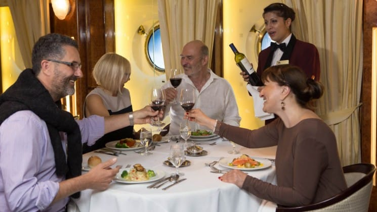 Server with wine watches as four friends toast in dining room aboard Sea Spirit expedition ship