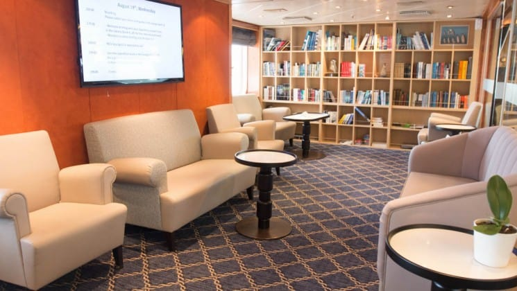 Library with bookcases, couches, chairs and tables aboard Sea Spirit expedition ship
