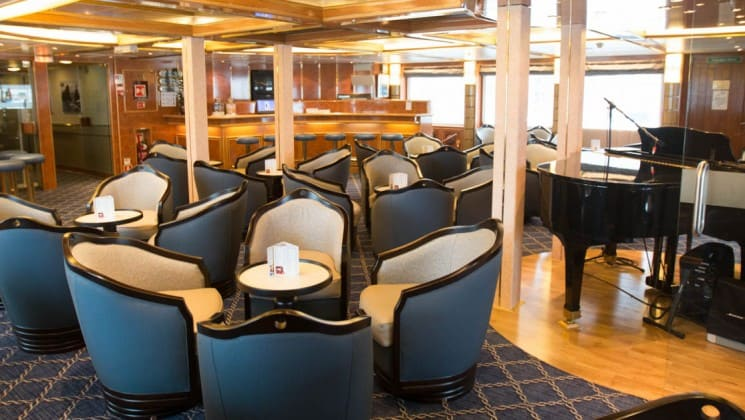 Tables and chairs near piano and bar in lounge aboard Sea Spirit small ship