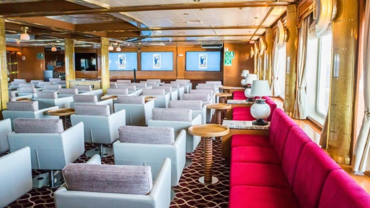 Couches and chairs set up in lounge with window-lined walls aboard Sea Spirit expedition ship