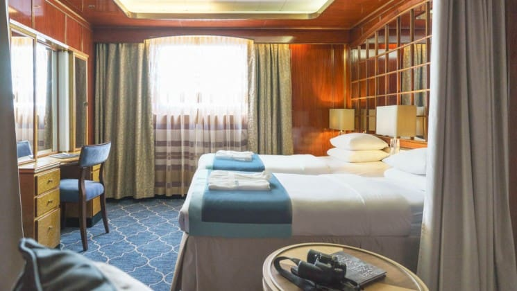 Two beds, small table, desk, chair and large window in Classic Suite aboard Sea Spirit small ship