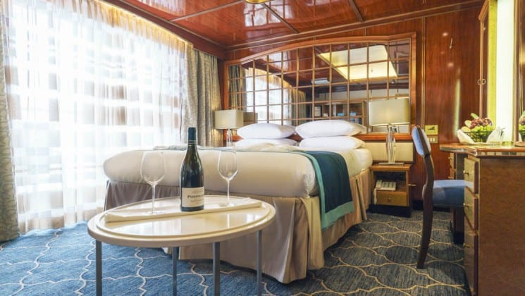 Wine bottle and glasses on small table beside bed, desk and chair in Deluxe Suite aboard Sea Spirit small ship