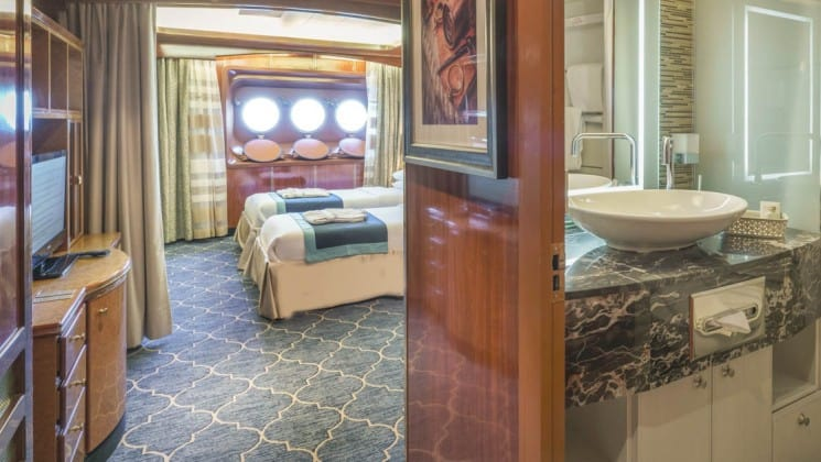 Entryway of Main Deck Suite with bathroom, two beds, desk and three portholes aboard Sea Spirit small ship