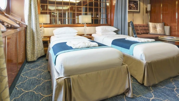 Two beds, couch and table in Main Deck Suite aboard Sea Spirit expedition ship