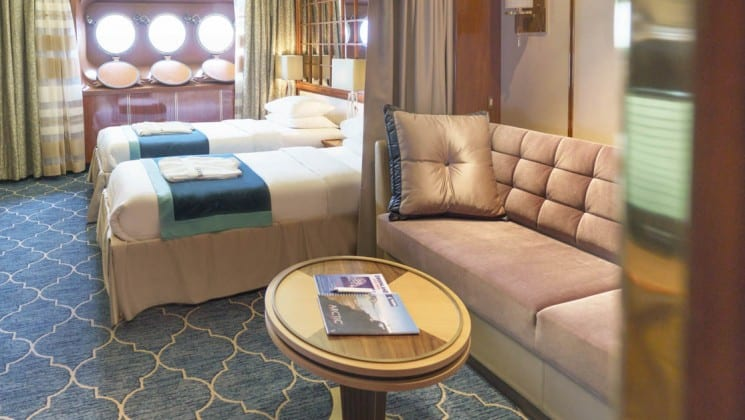 Couch, table, two beds, three portholes in Main Deck Suite aboard Sea Spirit small ship