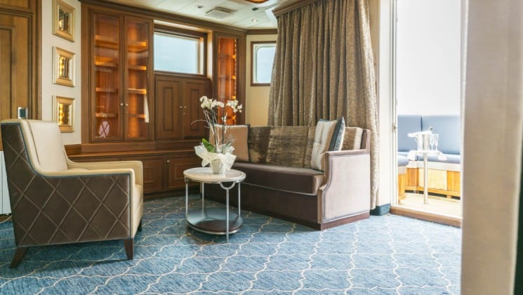 Sitting room with couch, armchair and coffee table in Owner's Suite aboard Sea Spirit small ship