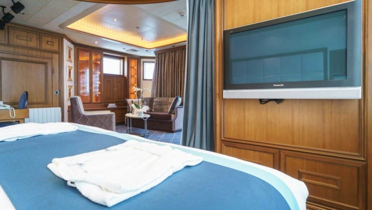 Large bed and TV with sitting area in background in Owner's Suite aboard Sea Spirit expedition ship