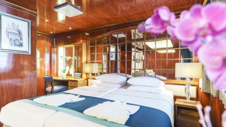 Large bed, two nightstands, desk and chair in Premium Suite aboard Sea Spirit expedition ship