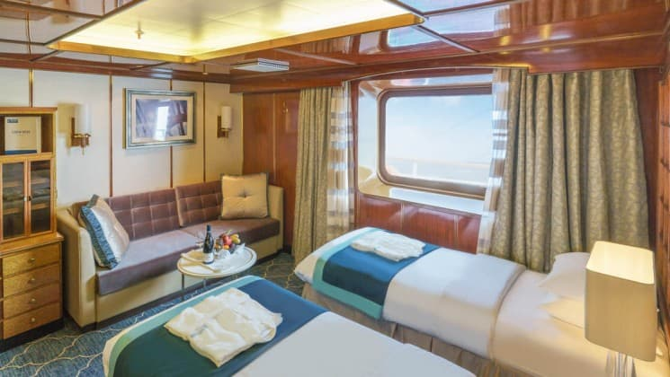 Two beds, couch, table and large windows in Superior Suite aboard Sea Spirit expedition ship