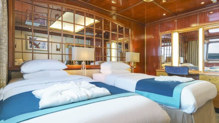 Two beds, desk, chair and large window in Superior Suite aboard Sea Spirit expedition ship