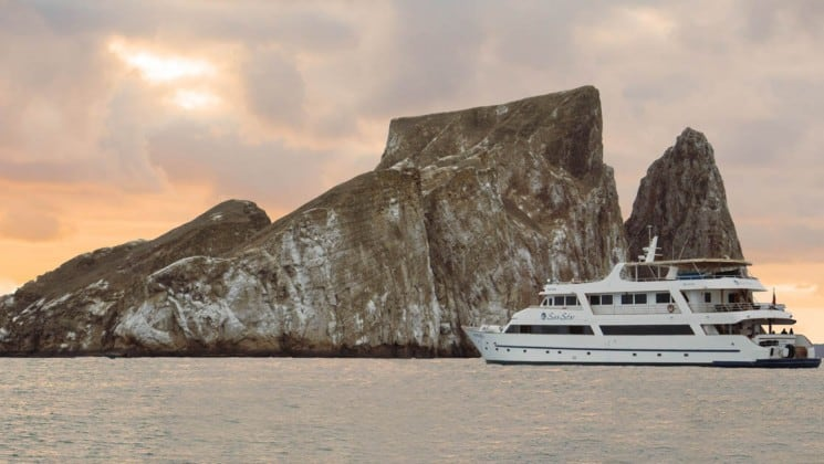 Sea Star Journey luxury yacht cruises by small rocky island in Galapagos Islands