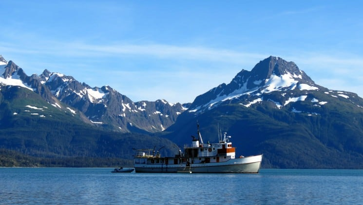 Full view of Sea Wolf yacht's starboard side with large Alaska mountains in background