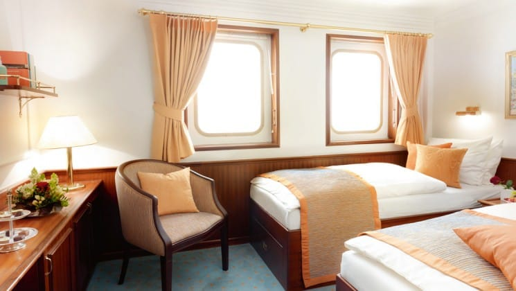 cabin with 2 large winodws, a desk and chair, and 2 beds aboard the Lindblad Sea Cloud luxury Mediterranean small ship