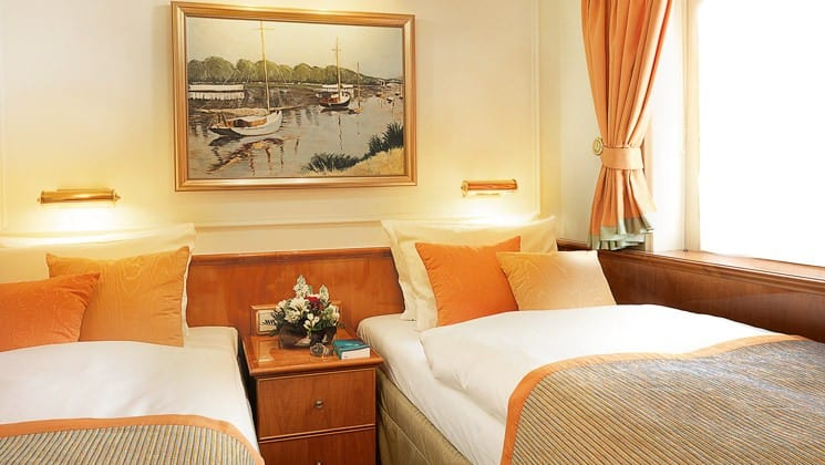 cabin with 2 beds, a nightstand with flowers, a large window and a painting on the wall of the Lindblad Sea Cloud mediterranean luxury small ship