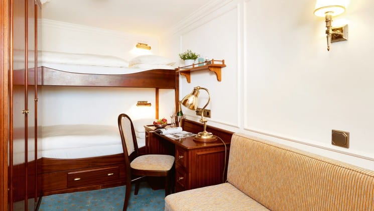Lindblad sea cloud mediterranean luxury yacht cabin with bunk beds, a chair and a desk