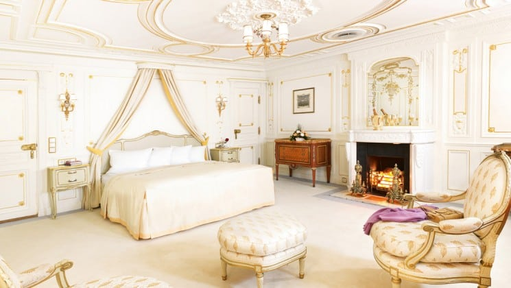 all white room with a large bed, ottomans and fireplace aboard the Sea Cloud mediterranean luxury yacht