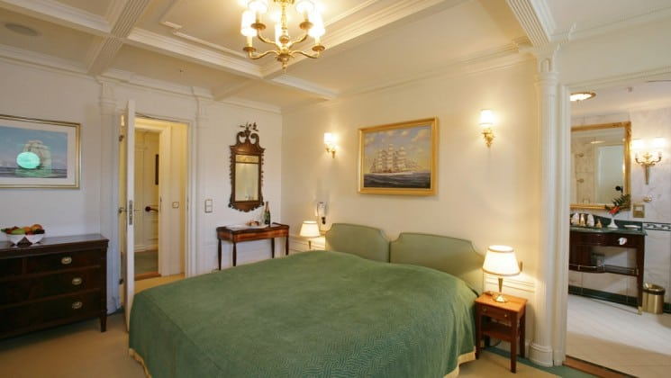 cabin with large green bed, desk and entrance to an adjoining room aboard the Lindblad Sea Cloud luxury mediterranean small ship