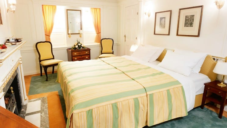 cabin with large striped bed, chairs, window and pictures on the wall aboard the Lindblad Sea Cloud mediterranean yacht