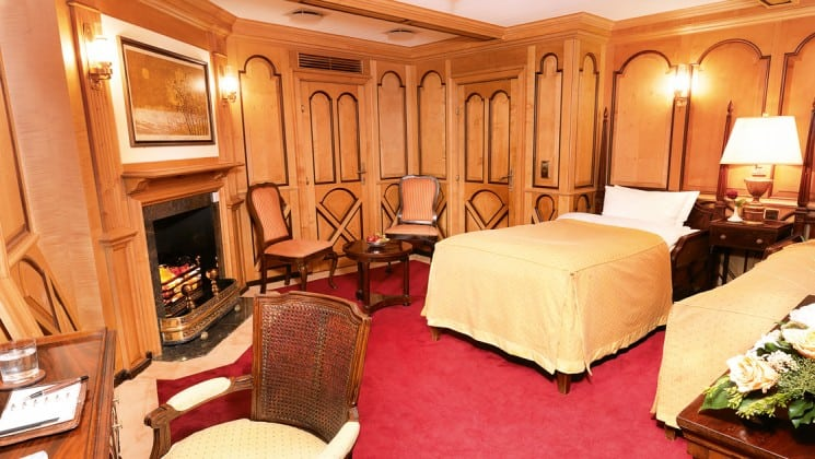 cabin with large bed, red carpet, fireplace and desk aboard the Lindblad Sea Cloud luxury yacht in the mediterranean