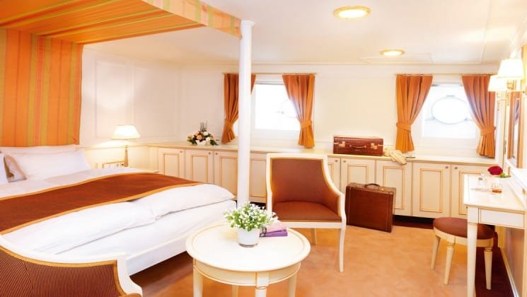 category c cabin with a large bed, table and chairs aboard the Lindblad Sea Cloud luxury mediterranean yacht