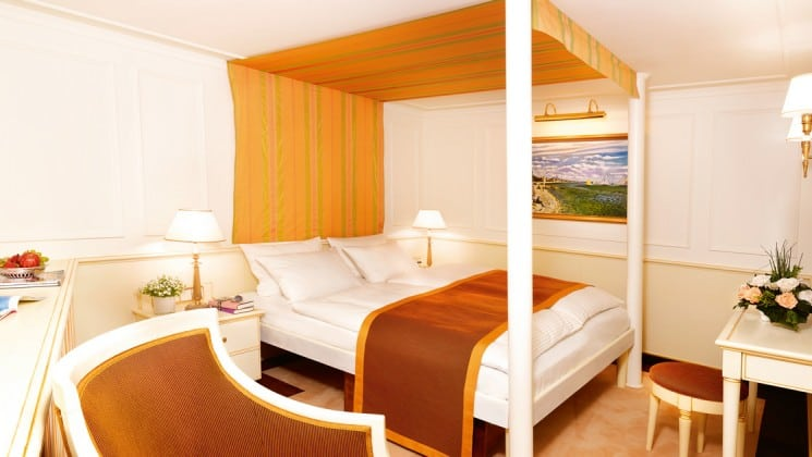 cabin with a large bed with 4 posts, table and chairs aboard the Lindblad Sea Cloud luxury mediterranean yacht