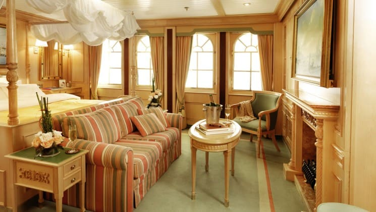 room with comfortable couch and large windows lining the walls aboard the sea cloud ii mediterranean luxury yacht