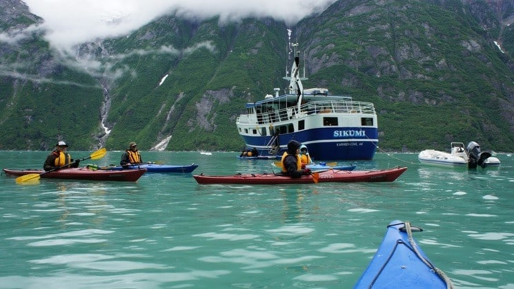 Kayakers in Alaskan waters off the stern of Sikumi yacht