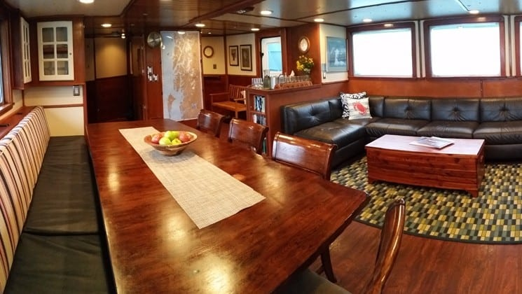 Large couch and table with chairs in lounge aboard Sikumi small ship in Alaska