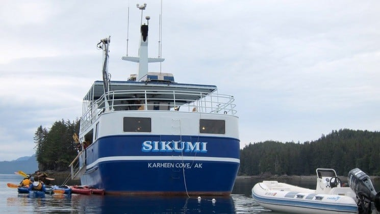 Kayakers paddle near stern of Sikumi yacht in Alaska