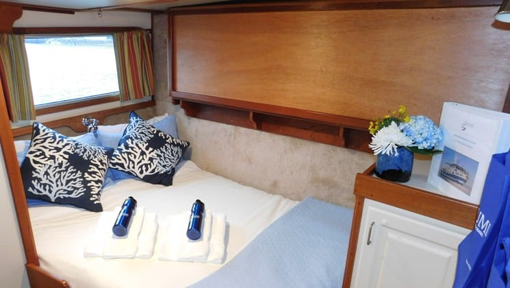 Bed, dresser, window in cabin aboard Sikumi small ship Alaska cruise