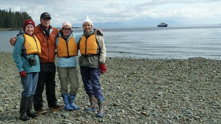 Four guests on shore with distant view of Sikumi yacht in Alaskan waters